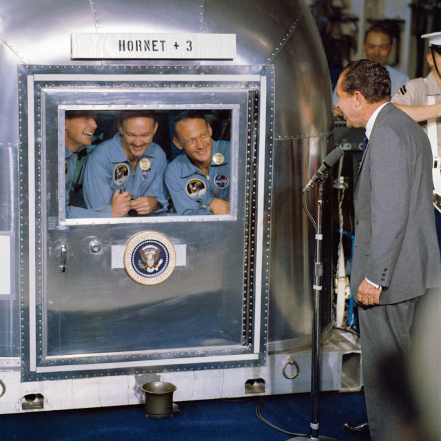 "(July 24, 1969) President Richard M. Nixon was in the central Pacific recovery area to welcome the Apollo 11 astronauts aboard the U.S.S. Hornet, prime recovery ship for the historic Apollo 11 lunar landing mission. Already confined to the Mobile Quarantine Facility (MQF) are (left to right) Neil A. Armstrong, commander; Michael Collins, command module pilot; and Edwin E. Aldrin Jr., lunar module pilot. Apollo 11 splashed down at 11:49 a.m. (CDT), July 24, 1969, about 812 nautical miles southwest of Hawaii and only 12 nautical miles from the U.S.S. Hornet. The three crewmen remained in the MQF until they arrive at the Manned Spacecraft Center's (MSC) Lunar Receiving Laboratory (LRL). While astronauts Armstrong and Aldrin descended in the Lunar Module (LM) ""Eagle"" to explore the Sea of Tranquility region of the Moon, astronaut Collins remained with the Command and Service Modules (CSM) ""Columbia"" in lunar-orbit."