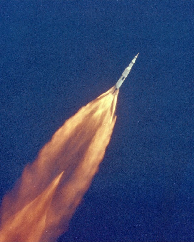 The Apollo 11 Saturn V space vehicle climbs toward orbit after liftoff from Pad 39A at 9:32 a.m. EDT on July 16, 1969. In 2 1/2 minutes of powered flight, the S-IC booster lifts the vehicle to an altitude of about 39 miles some 55 miles downrange. This photo was taken with a 70mm telescopic camera mounted in an Air Force EC-135N plane. Onboard are astronauts Neil A. Armstrong, Michael Collins and Edwin E. Aldrin, Jr.