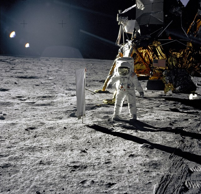 "Astronaut Edwin E. Aldrin, Jr., Lunar Module pilot, is photographed during the Apollo 11 extravehicular activity (EVA) on the lunar surface. In the right background is the Lunar Module ""Eagle."" On Aldrin's right is the Solar Wind Composition (SWC) experiment already deployed. This photograph was taken by Neil A. Armstrong with a 70mm lunar surface camera."