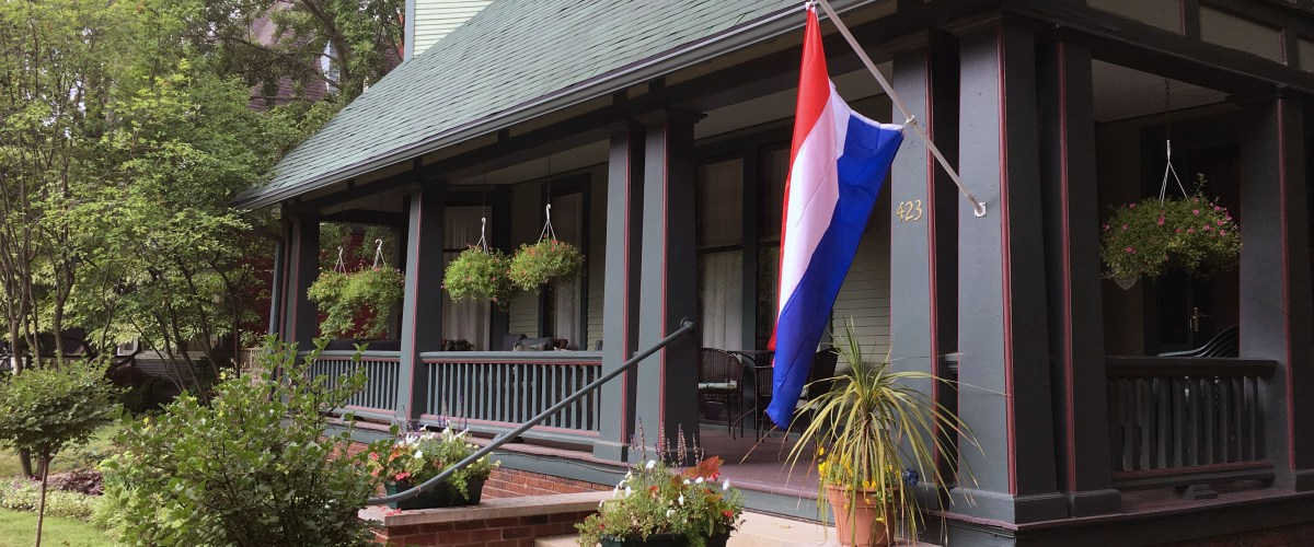 Exterior view of front porch with a Dutch flag on the house