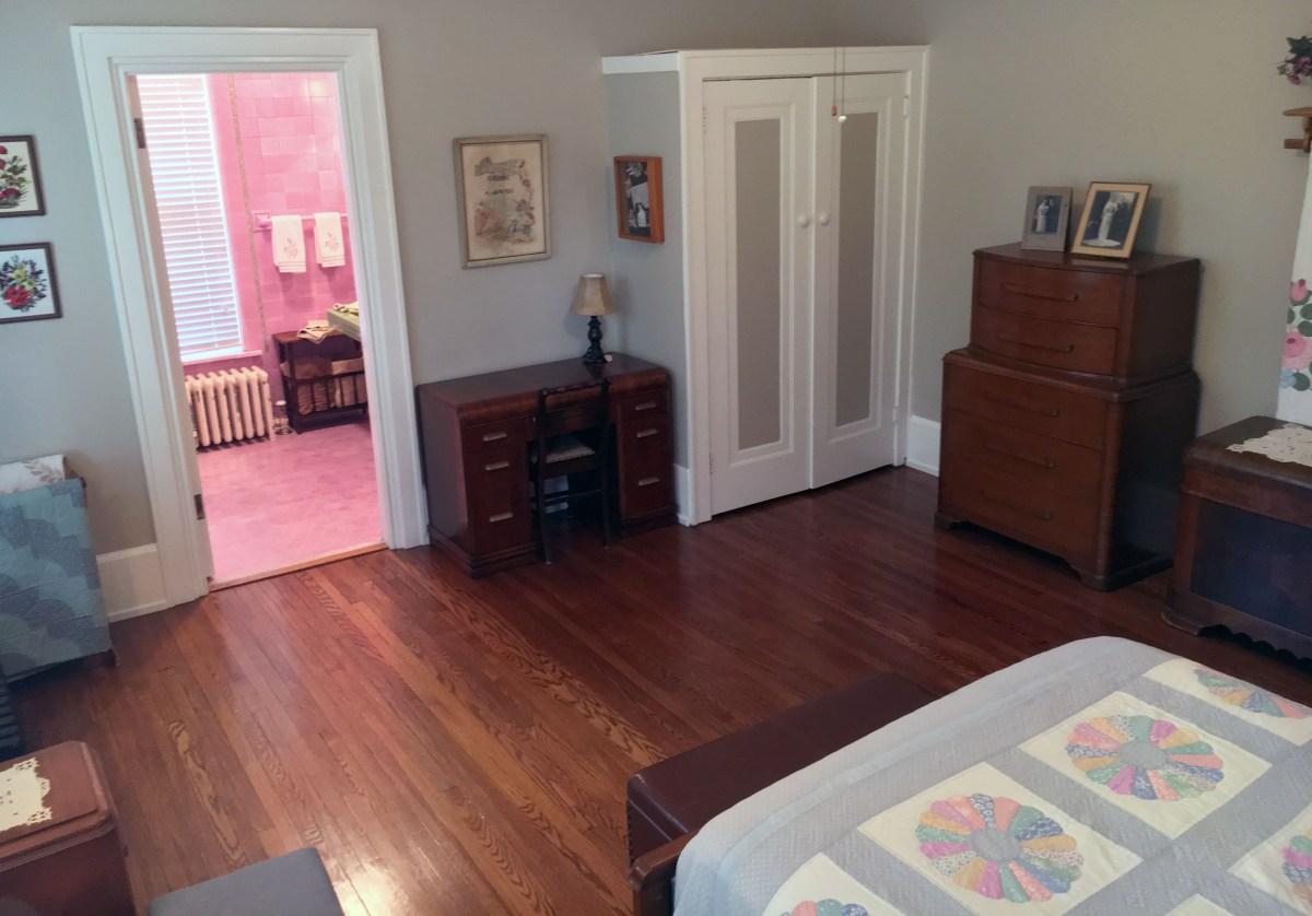 foot of queen bed, desk, and bathroom doorway in room 3
