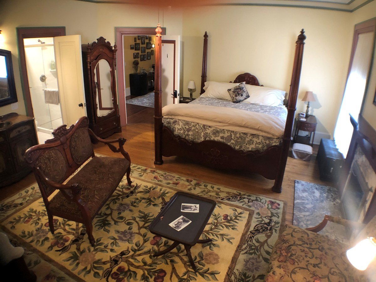 View of room 1 including love-seat, bed, and bathroom door