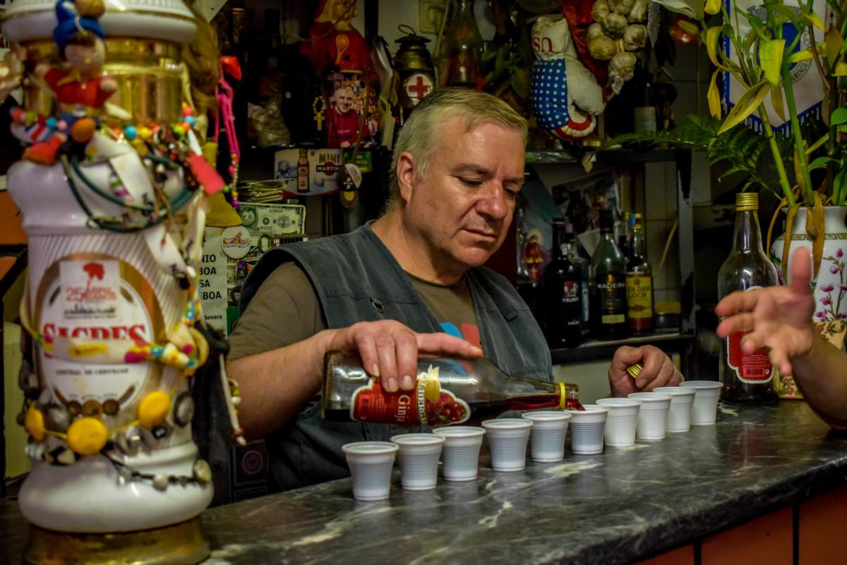 Barman serving Ginjinha liqueur in Lisbon Portugal