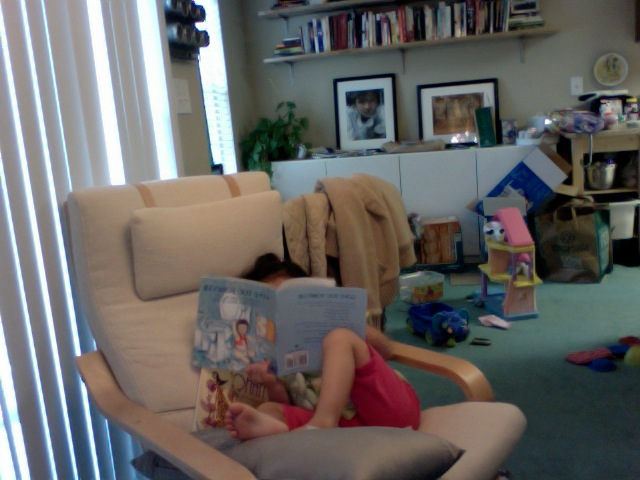 """i love it when roenne """"reads"""" by herself. she's been lounging in that chair and reading for 20 min now. =)"""