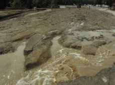 The force of Boulder Creek carved foot-deep canyons into an asphalt parking lot just above the creek banks,