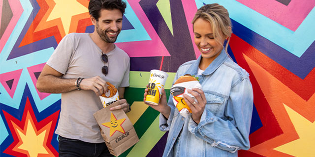 two people stood in front of a colourful wall with Carl Jr food