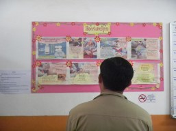 4.23 - Vientiane - MCH - man reviewing baby care poster