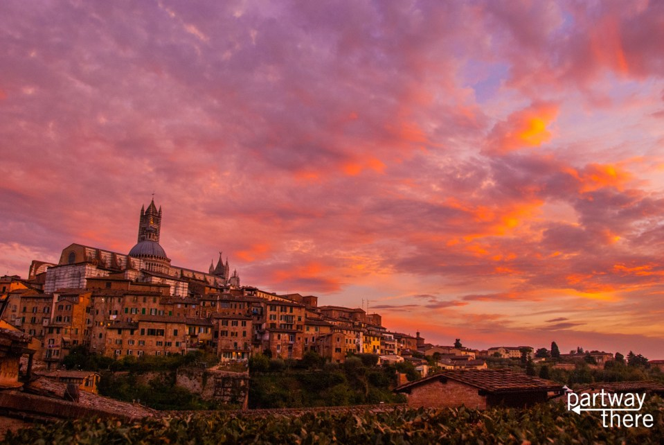 Red, orange and pink sunset vista in Siena, Italy with Siena Duomo