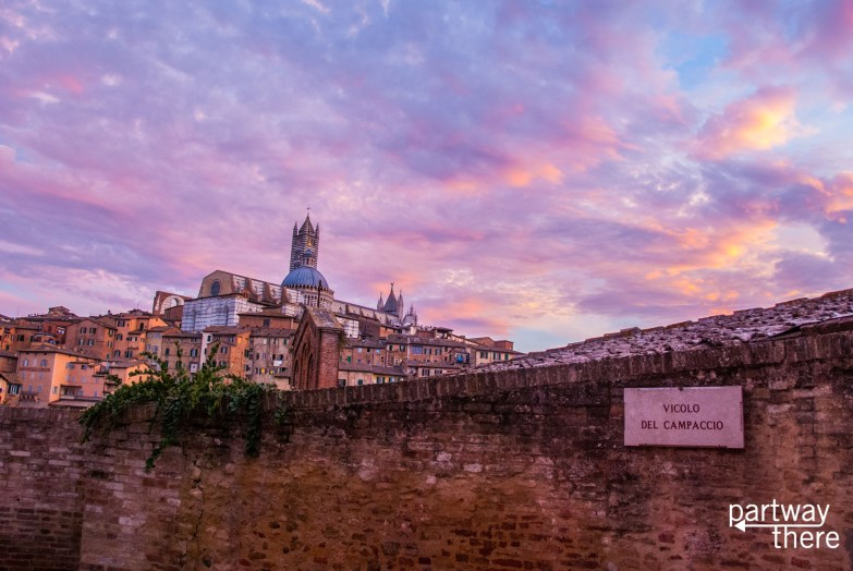Viccolo del Campaccio road in Siena, Italy, with view of city at sunset