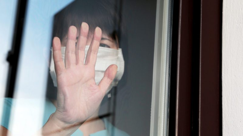 An image showing a sad woman in a face mask looking out of a window