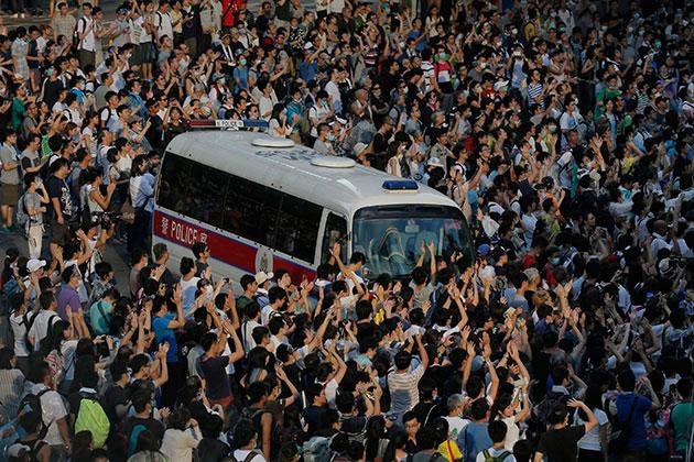 Hong Kong protestors overwhelm a police vehicle.