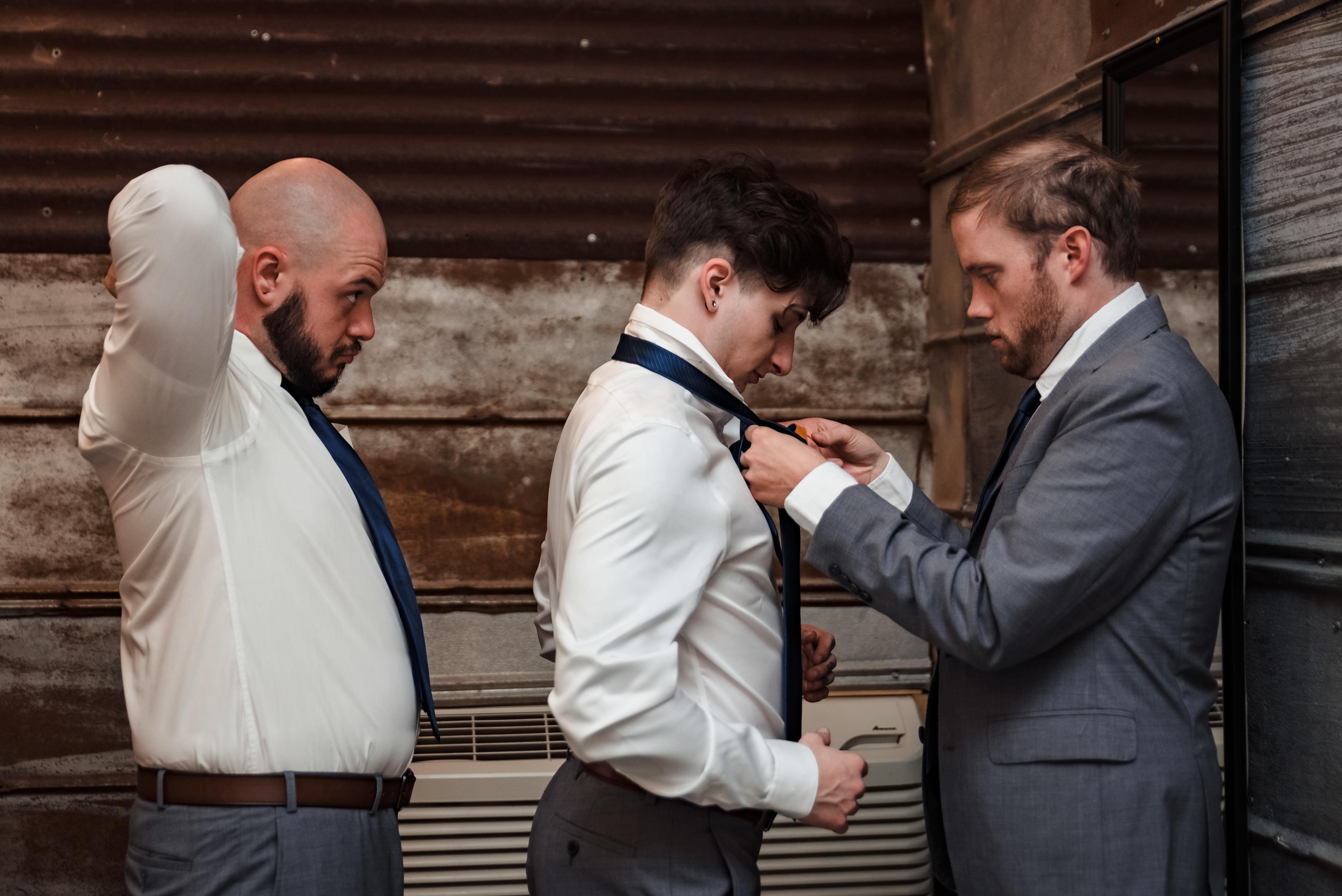 Groom helping groomsmen put on ties