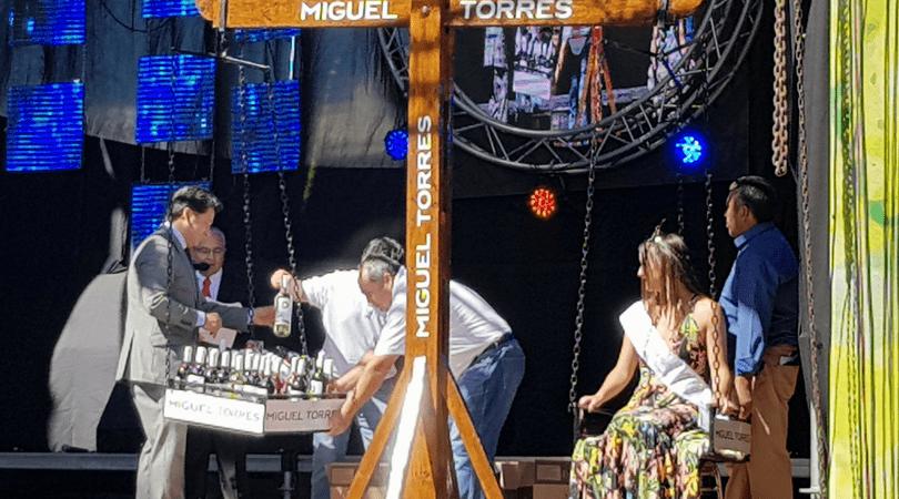 Pesaje de la reina Ignacia Rivera Burgos en una balanza que es contrapesada con botellas de vino