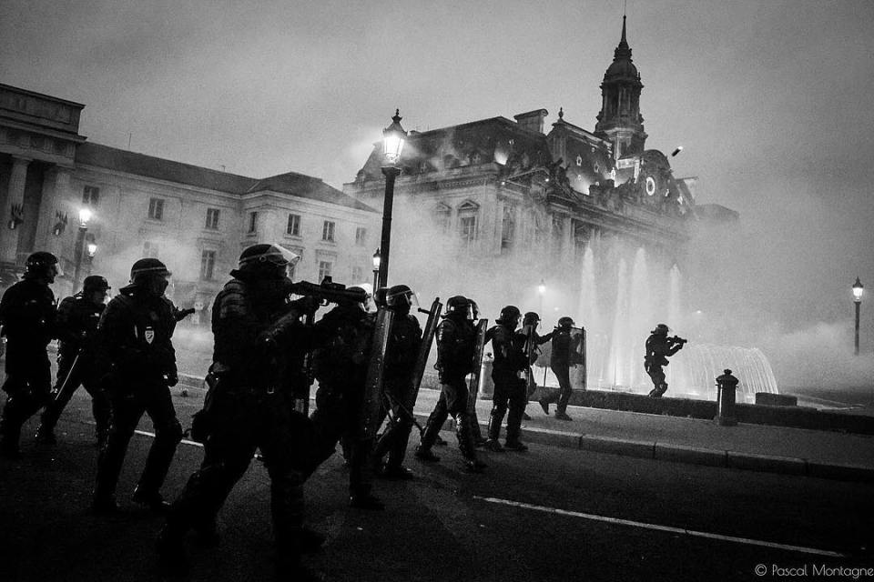 9th act from yellow vests. Policemen at work during the sunset. Pascal Montagne for @37degres . #yellowvests #yellowjacket #taxes #arrested #government #demonstration #blackandwhite #bnwphotography #instablackandwhite #bnw #fog #teargas #building #policemen #fight