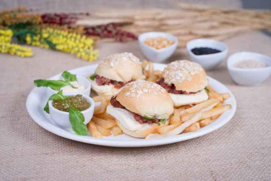 Mini Burguer da Valentina Três minis hambúrgueres de calabresa com queijo meia cura, rúcula, no pão de aveia. Acompanha maionese, geléia de pimenta e batata frita. Bar Oscar Grill Divulgação