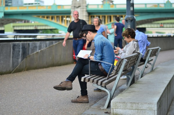 A sunny day in London... and tourists and locals busy walking , sitting, and reading...