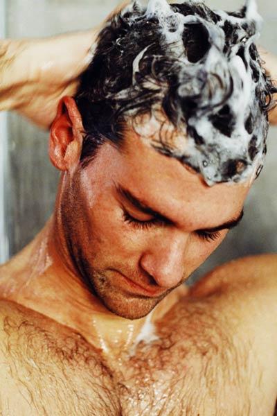 homme se faisant un shampoing antipelliculaire
