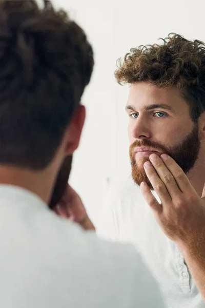 homme appliquant de l huile de coco sur sa barbe
