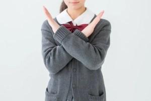 バツサインをする女子生徒