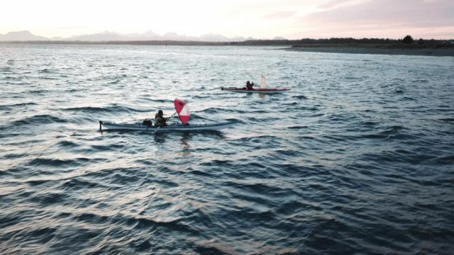 two kayakers sailing at dusk