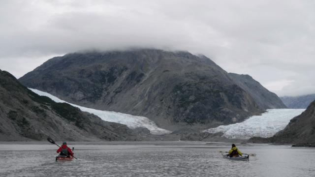 two kayakers paddling toward a retreating glacier in Alaska