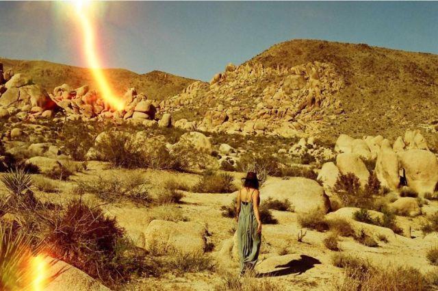 woman walking through desert with light leak