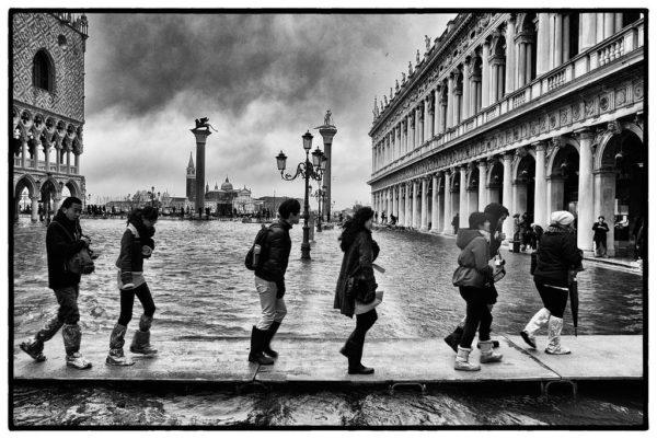 Tourists walk along a Venetian canal