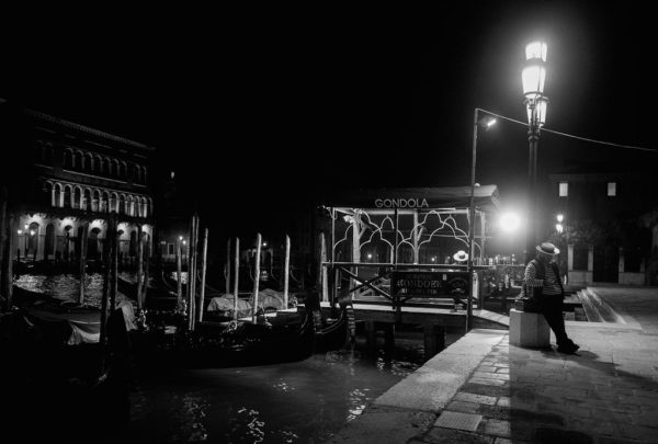 A gondolier leans against a lamppost on a Venice evening