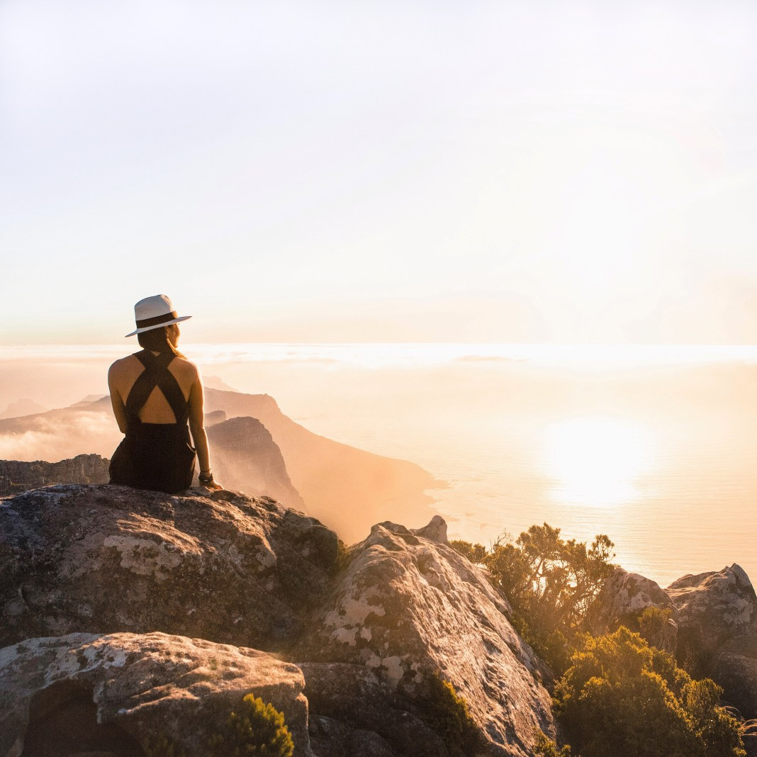 Woman with Hat Sitting on Lion's Head during Sunrise in Cape Town, South Africa