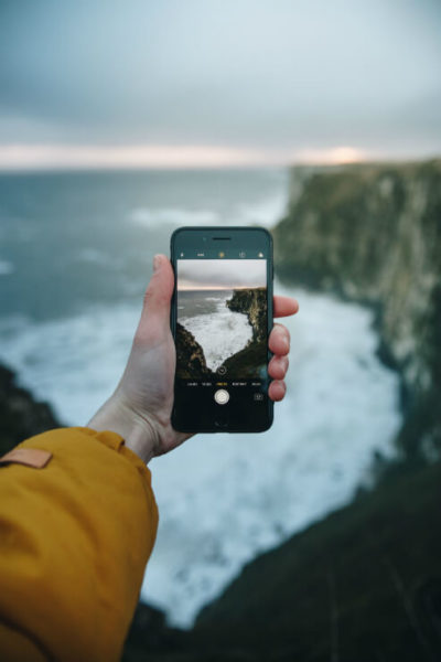 Persons hand holds mobile phone taking photo of seaside cliffs