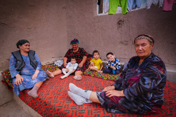 Women and children in Central Asia pose in their home.