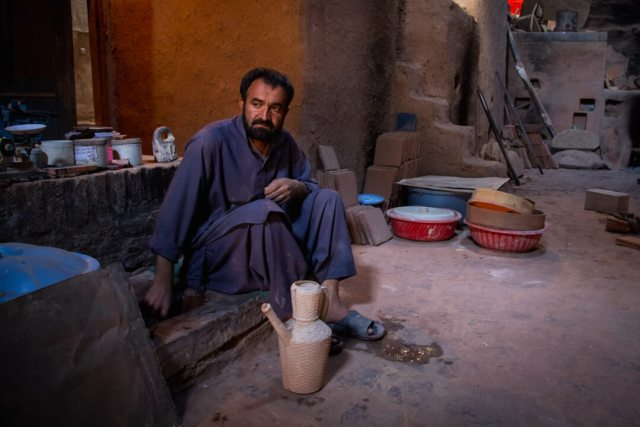 A tradesman sits around his wares on a street in central asia.