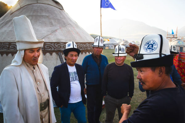 tribesmen in central asia pose before their yurt.