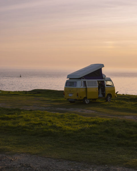 a van parked by the sea at dusk.