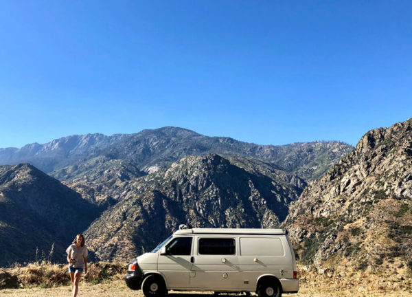 a girl and white van in front of mountains on an american road trip
