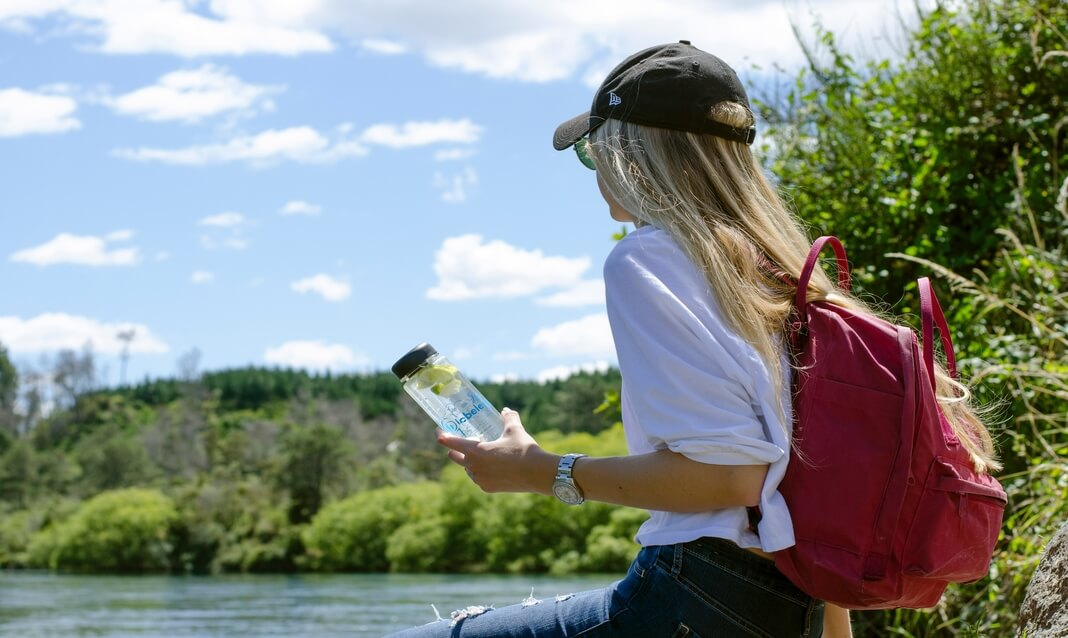 woman holding recycled plastic water bottle