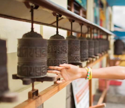 a child's hand spins a buddhist prayer wheel