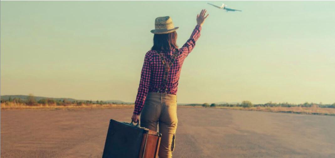 woman traveler waving at airplane