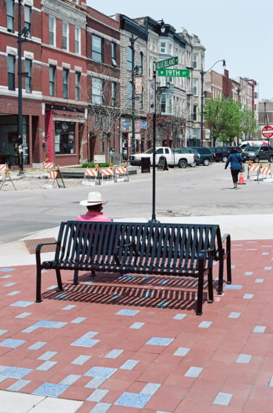 man in cowboy hat on city bench