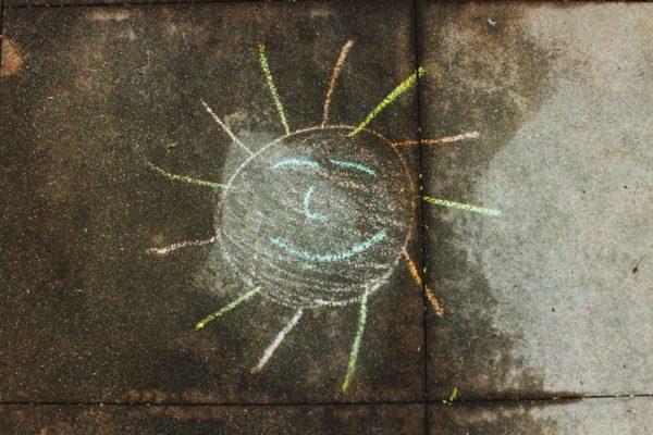 smiling sun chalk ark on sidewalk