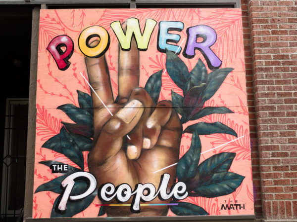 power to the people mural with hand raising peace sign