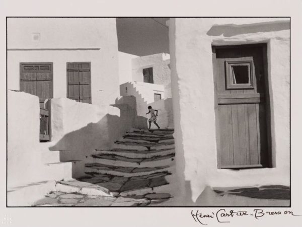 black and white photograph person running up adobe stairs