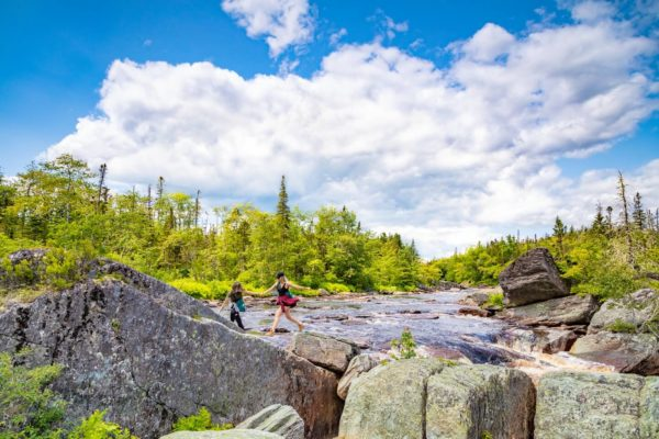 hikers clambering over river rocks in eastern shore of nova scotia