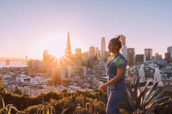travel nurse walking in front of metropolitan skyline