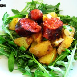 Roasted potato on a bed of rocket topped with chorizo