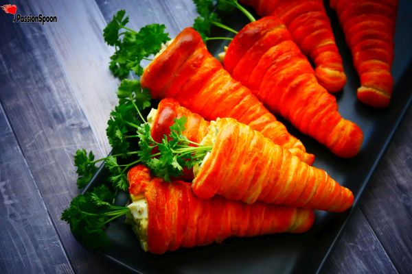 Orange gold and puffy croissants in a form of carrots filled with egg salad and garnished with parsley sprigs.