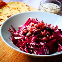 Lovely purple radicchio topped with sizzling vinegar bacon and beans. Homemade garlic Naan bread and yoghurt dip in the background.