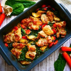 Spinach and artichokes chicken thighs in a ceramic baking dish. Carrots and fresh spinach on a side for deco.