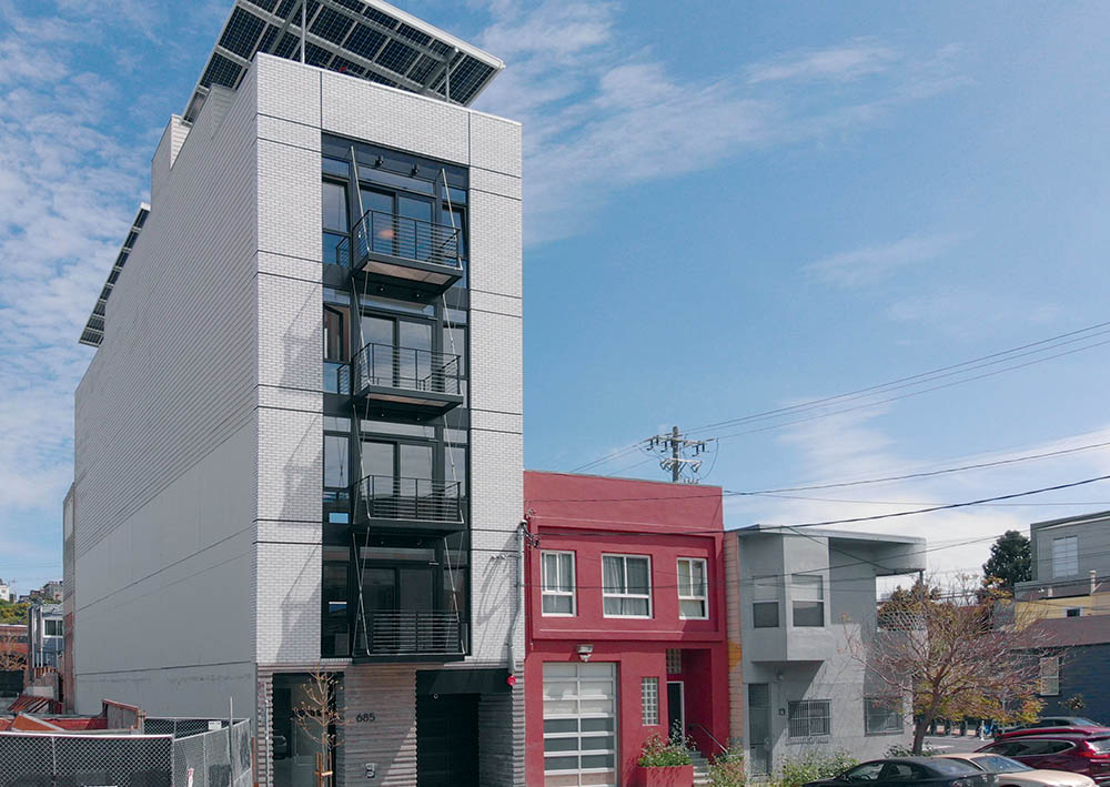 Sol Lux Alpha - exterior facade shot from a distance, clear blue sky