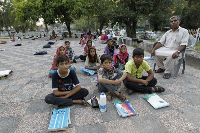 Master Mohammad Ayoub poses with his fifth-grade students at a local park in Islamabad, Pakistan. Caren Firouz  Reuters